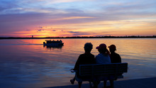 Silhouette Of 3 Senior Women Enjoying A Colorful Sunset On A Bench At A Beautiful Lake As A Pontoon Passes By.
