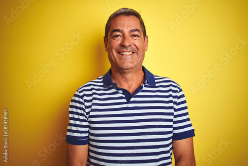 Fototapeta Handsome middle age man wearing striped polo standing over isolated yellow background with a happy and cool smile on face. Lucky person. obraz na płótnie