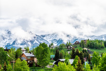 Mt Crested Butte, USA Colorado Village In Summer With Clouds And Foggy Mist Sunrise Morning And Houses On Hills With Green Trees