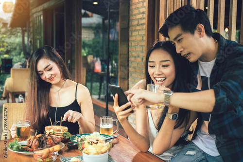 Asian single woman envious with love couple doing take selfie at restaurant Fototapet
