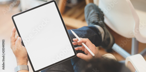 Young male freelancer reading and holding blank screen tablet Fototapeta