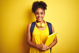 Afro woman using backpack and headphones holding notebook over isolated yellow background with a happy face standing and smiling with a confident smile showing teeth