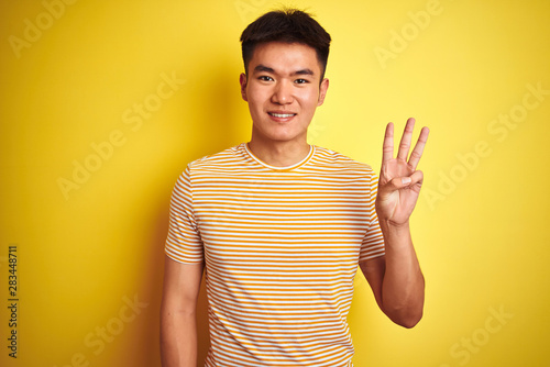 Fototapeta Young asian chinese man wearing t-shirt standing over isolated yellow background showing and pointing up with fingers number three while smiling confident and happy