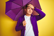 Asian Chinese Man Wearing Purple Umbrella Standing Over Isolated Yellow Background Stressed With Hand On Head, Shocked With Shame And Surprise Face, Angry And Frustrated. Fear And Upset For Mistake.
