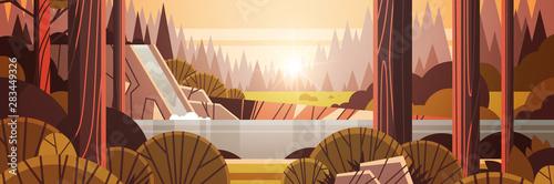 Fototapeta beautiful waterfall over rocky cliff yellow autumn forest nature landscape sunset background flat horizontal obraz