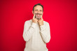 Leinwandbild Motiv Handsome middle age senior man with grey hair over isolated red background Smiling with open mouth, fingers pointing and forcing cheerful smile
