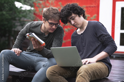 Two teenagers doing homework with books and a cosplayer sitting outdoors in a pa Canvas Print