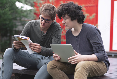 Two teenagers doing homework with books and a cosplay, sitting on the street on Wallpaper Mural