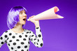 canvas print picture - Beautiful girl in violet wig is shouting into pink paper loudspeaker. Stylish fashionable woman is speaking out loud. Bright young female on purple background. Good mood, fun and gladness concept.