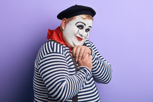Portrait Of A Shy And Flirty Fat Mime Giving Admiring Look. Man Falls In Love, Holding Hands Clasped And Feeling Awkward. Romantic Comedy Concept.isolated Blue Background, Studio Shot