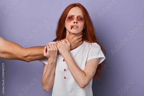 Fototapeta  scared woman trying to stop her angry husband who wants to kill her