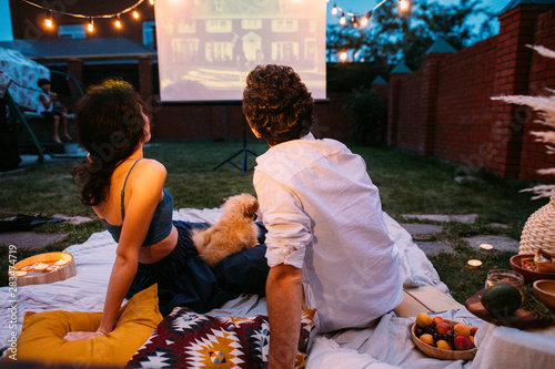 Foto Couple in love watching a movie, in twilight, outside on the lawn in a courtyard