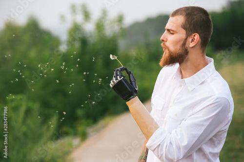 Photo Young Man With Artificial limb is holding dandelion and blowing on it
