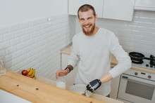 Young Bearded Smiling Guy With Artificial Limb  Cooks In The Kitchen