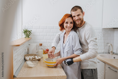 Fotografia  A young man with artificial limb is cooking in the kitchen with his girlfriend