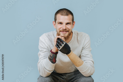 Photo Young Man With Artificial hand is looking forward and smiling at the camera