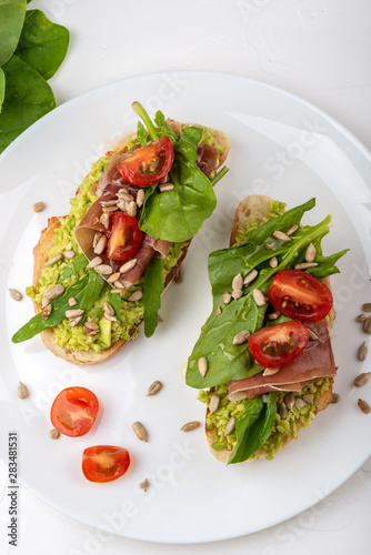 Spoed Fotobehang Voorgerecht Sandwich with prosciutto, jamon, tomatoes and avocado on white background.