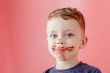 Little Boy Eating Chocolate. Cute Happy Boy Smeared With Chocolate Around His Mouth. Child Concept.