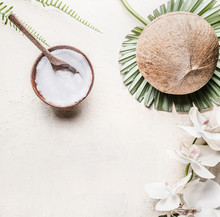 Coconut Oil Or Butter In Wooden Bowl With Spoon And Whole Coconut On Tropical Leaves And Flowers, Top View . Copy Space . Healthy Plant Based Fat Source. Vegan Food And Cosmetic