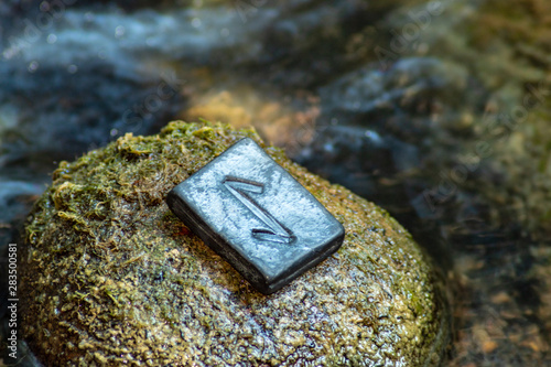 Photo Norse rune Eihwaz on the stone and the evening river background