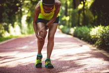 Female Runner Suffering With Sports Injury On Running
