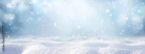 Fototapeta Winter snow background with snowdrifts, with beautiful light and snow flakes on the blue sky, beautiful bokeh circles, banner format, copy space. obraz na płótnie