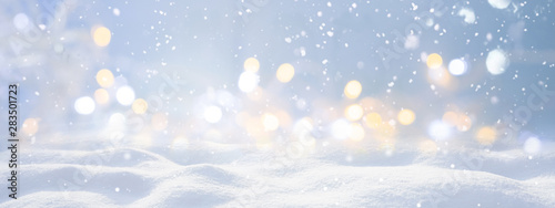 Obraz Festive Christmas natural snowy landscape, abstract empty stage, background with snow, snowdrift and defocused Christmas lights. Blue and yellow Golden Christmas lights against blue sky, copy space. - fototapety do salonu