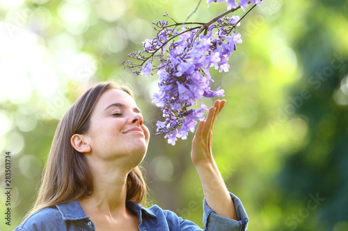 Fototapeta Candid woman smelling flowers in a park obraz