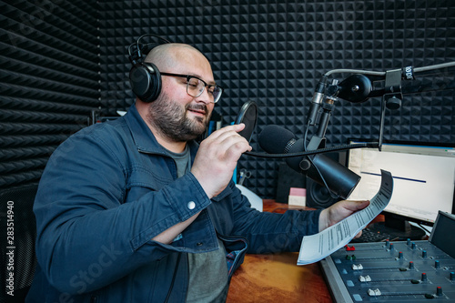 Fototapeta  Smiling male radio presenter read text on paper in radio station