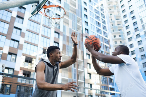 Vászonkép  Two sportive African-American men playing basketball in urban setting, copy spac