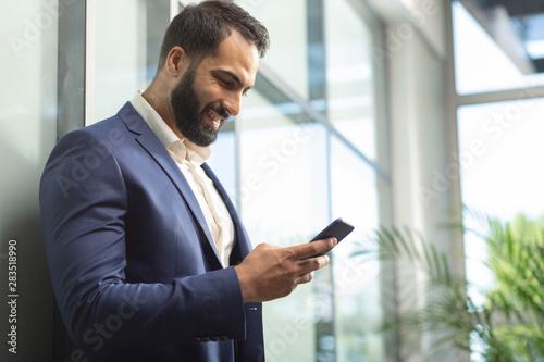 Kind bearded office worker reading good news