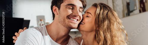 Fotografie, Obraz  panoramic shot of charming girl kissing boyfriend in cheek in kitchen