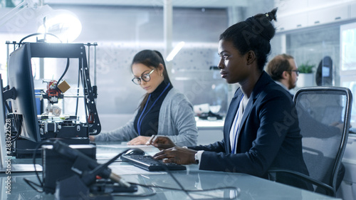 Foto  Black Female Scientist Working on a Computer with Her Colleagues at Research Center
