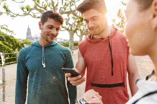Foto  Photo of attractive smiling people using cellphone and stopwatch while working o