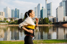 Photo Of Sporty Slim Woman Running While Working Out Near City Riverfront