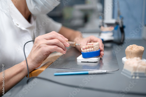 Professional prosthetic technician making dental porcelain for the patient.