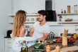 sexy couple looking at each other near table with vegetables in kitchen