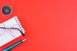 Leinwanddruck Bild - Notizblock Kugelschreiber und Brille auf einem roten Hintergrund