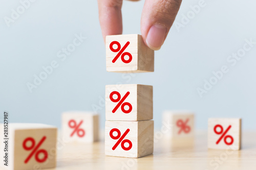 Fototapeta Interest rate financial and mortgage rates concept. Hand putting wood cube block increasing on top with icon percentage symbol upward direction obraz