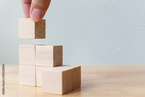 Obraz Hand arranging wood block stacking as step stair on wooden table. Business concept for growth success process. Copy space - fototapety do salonu