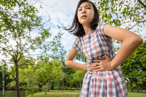 Asian little girl holding her hands on belly,suffers from stomachache, cute chil Canvas-taulu