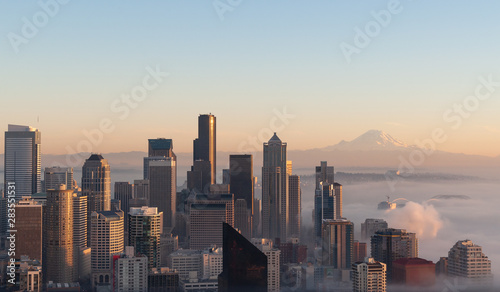 Photo  Partially immersed in the mist caming from Elliott Bay, this panoramic view of Seattle at sunset, was taken in a cold autumn day, with blue sky and the Mount Rainier visible on the background