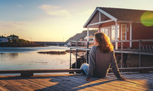 Beautiful Young  Girl Traveler Sitting On Wooden Pier On The Background Of Traditional Red Rorbu Traveling To Lofoten Norway