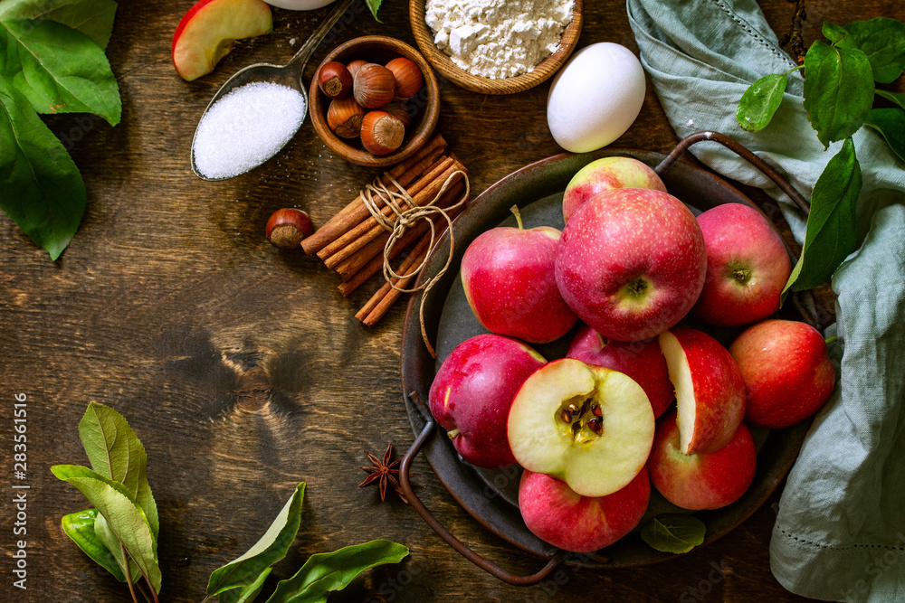 Fototapety, obrazy: Apple baking seasonal concept. Ingredients for apple pie (red apple, flour, eggs, anise, hazelnut, sugar and cinnamon) on a rustic wooden table. Free space for your text.