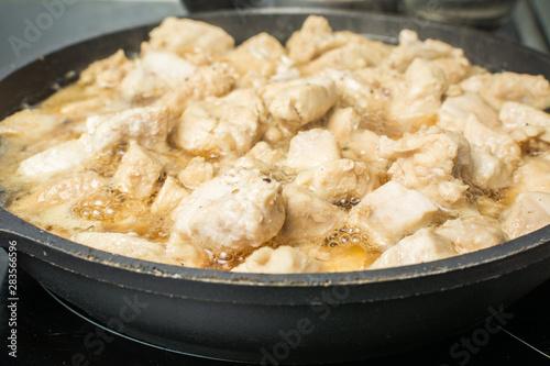 Fototapeta Slices of juicy chicken with gravy stew in pan on stove. obraz