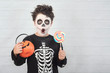 Leinwanddruck Bild Happy Halloween.funny child in a skeleton costume eating lollipop in halloween