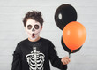Leinwanddruck Bild Happy Halloween. funny child in a skeleton costume with colorful balloons