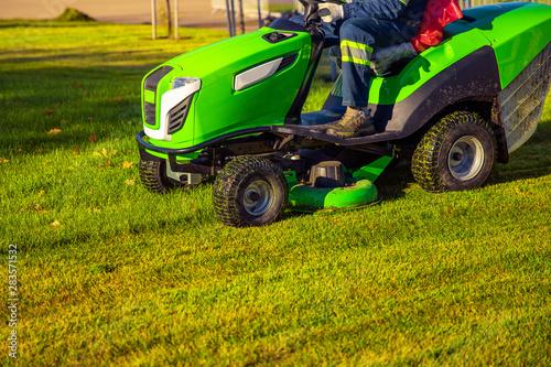 Fototapeta Gardener worker on lawn mower tractor cuts green grass obraz
