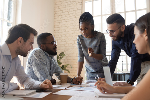 Photo Serious multiracial corporate business team discuss paperwork at group briefing
