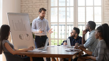 Serious Male Coach Give Flip Chart Presentation To Diverse Employees